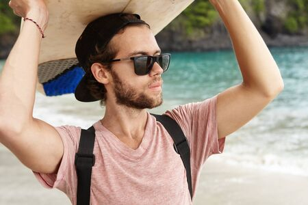 bodyboarding: Hobby and vacation. Handsome young man with beard wearing stylish sunglasses and snapback holding surfboard over his head, looking away at ocean, waiting for big waves, standing on beach alone Stock Photo