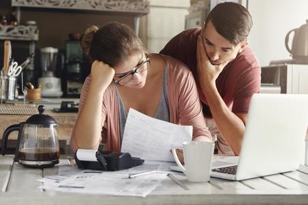 Jonge beklemtoonde Kaukasische paar geconfronteerd met financiële problemen, zittend op de keuken tafel met papieren, rekenmachine en laptop computer en het lezen van documenten van de bank, op zoek gefrustreerd en ongelukkig