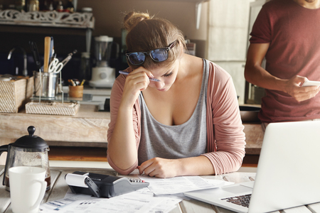 Depressed couple facing credit problem. Stressed wife looking exhausted while doing accounts at home, trying hard to cut family expenses, holding pen and making necessary calculations on calculator Stock Photo
