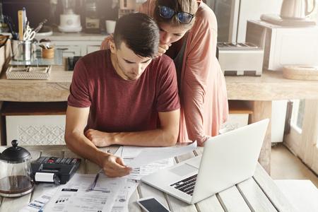 Młode rodziny zarządzające budżetem, przeglądając swoje rachunki bankowe za pomocą ogólnego laptopa i kalkulatora w kuchni. Mąż i żona robi papierkową robotę wpólnie, płaci podatki online na notebooku