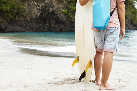 Cropped portrait of barefooted young surfer standing on sandy beach against high rocky shore with vegetation, carrying his white surfboard, ready to hit waves, spending summer vacations in tropics