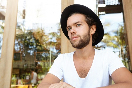 Close up view of attractive fashionable young bearded businessman in V-neck shirt and black hat sitting at sidewalk coffee shop while waiting for his partners, having serious and pensive look Stock Photo