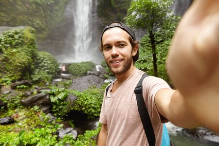 People, lifestyle, nature and adventure concept. Stylish young traveler with knapsack holding camera and shooting himself, recording video report of his journey for his blog, standing by waterfall