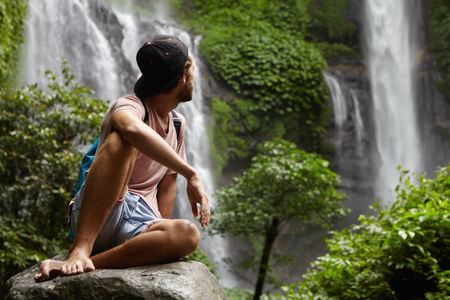 waterfall model: Nature, wildlife and travel concept. Young barefooted hiker wearing snapback sitting on big stone and enjoying beautiful view around him. Hipster relaxing deep in rainforest, looking at waterfall Stock Photo