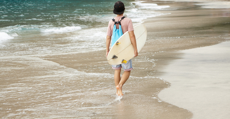 bodyboarding: Young barefooted surfer with backpack walking along beach, carrying white bodyboard under his arm, returning home after intensive ride, getting prepared for serious contest among wave riders