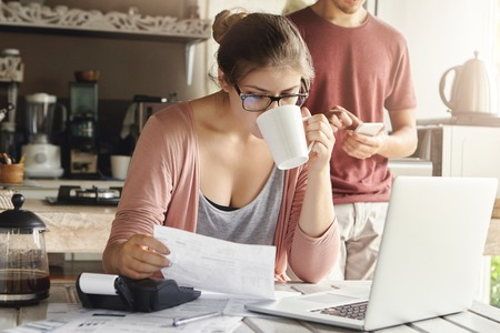 cuenta bancaria: Attractive serious female in spectacles drinking coffee and studying document in her hands, managing family budget and doing paperwork at kitchen table with pile of bills, laptop and calculator