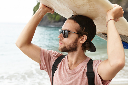Surfer lifestyle during summer travel vacation. Close up portrait of young attractive and handsome tanned Caucasian athlete wearing sunglasses going out surfing, carrying surf board on his head Фото со стока