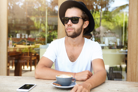 Fashionable young man in trendy sunglasses and white V-neck shirt having rest at sidewalk cafeteria, drinking cappuccino, sitting at wooden table with mug and mobile phone copy space screen on it Stock Photo