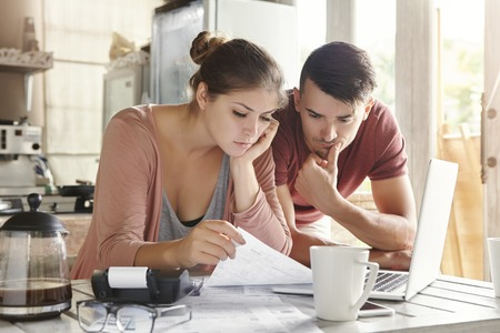 Worried young Caucasian married couple reading important notification from bank while managing domestic finances and calculating their expenses at kitchen table, using laptop computer and calculator Stockfoto