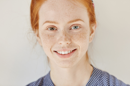 Close up portrait of beautiful young redhead model with different colored eyes and healthy clean skin with freckles smiling joyfully, showing her white teeth, posing indoors. Heterochromia in human Фото со стока - 70985340