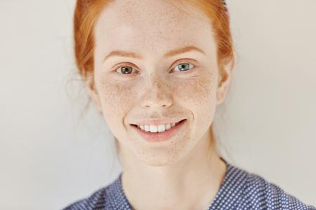 Sluit omhoog portret van mooi jong roodharigemodel met verschillende gekleurde ogen en gezonde schone huid met sproeten die vreugdevol glimlachen, die haar witte tanden tonen, die binnen stellen. Heterochromie bij de mens