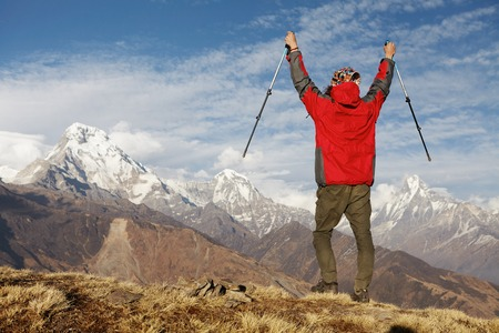 Elated and blissful young hiker cheering with his arms raised in the sky after trekking in highlands. Face to face with the majestic and grand Himalayan mountains with snowy summits and passes