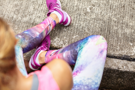 Top view of blonde female athlete in stylish leggings and purple sneakers sitting on sidewalk while relaxing after active running training in city park on summer day. Selective focus on girls feet