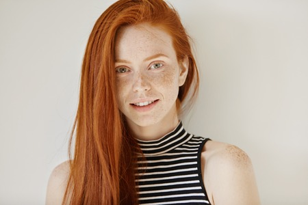 Fashion and beauty concept. Charming young female model with long ginger hairstyle and freckles dressed in striped top posing indoors and smiling happily at camera, showing her straight white teeth