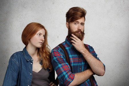 Young redhead female in denim jacket staring angrily at his narcissistic boyfriend who is having self-contented expression, touching his stylish fuzzy beard that he has just got trimmed in barbershop