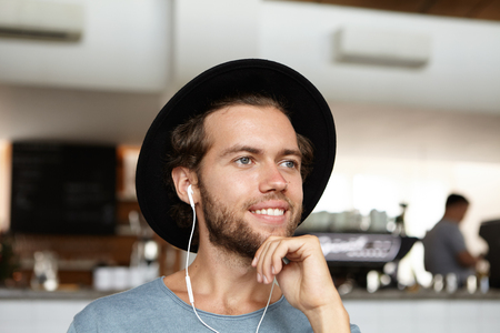 Headshot of handsome young bearded student in black hat smiling joyfully, enjoying free wifi, making video call to his girlfriend on earphones, using some electronic gadget during lunch at cafe Stock Photo