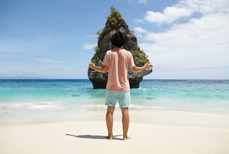 arms wide open: Rear view of tourist in trendy hat holding arms wide open in front of rocky island with tropical vegetation, admiring wonderful view, standing on beach with azure ocean water and blue sky on horizon Stock Photo