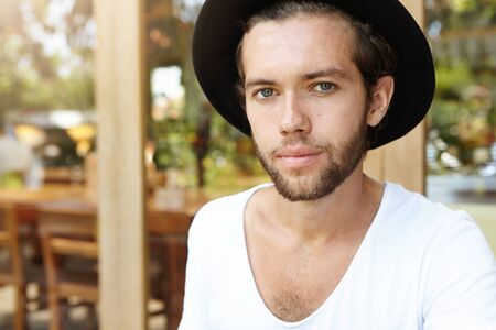Close up portrait of handsome young hipster with fuzzy beard wearing black hat and white t-shirt looking at camera with faint smile, rejoicing at hot summer days during his journey in tropical country