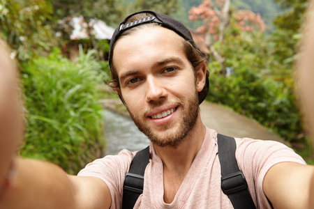 addressing: Stylish young bearded male blogger with backpack posing outdoors while recording video on front-facing camera of his gadget, addressing himself to his followers and telling them about his road trip Stock Photo