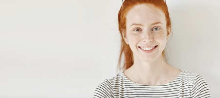 Heterochromia concept. Attractive young woman with ginger hair and different colored eyes smiling happily, posing isolated against white studio wall with copy space for your informational content Banco de Imagens - 70976550