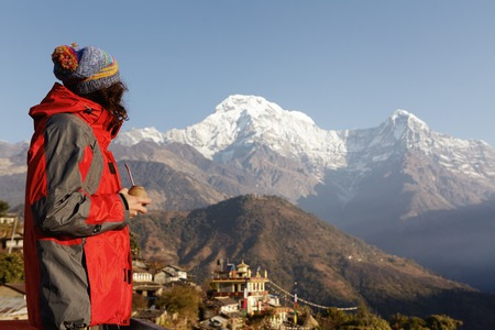 tibetan house: Side view of male tourist standing on top of cliff with calabash gourd in his hands, enjoying fresh made mate and contemplating picturesque view of grand mountains with its craggy summits and passes Stock Photo
