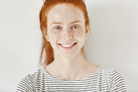 Close up highly-detailed portrait of happy and cheerful Caucasian female student with cute smile, ginger hair and perfect healthy freckled skin having rest indoors after lectures at university Stock Photo