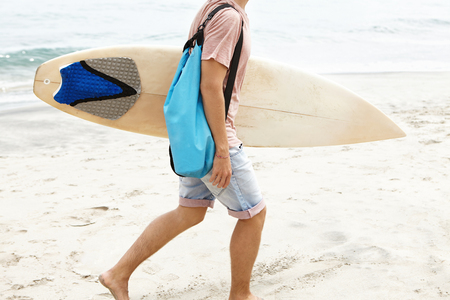 Cropped shot of barefooted man with blue bag carrying white surfboard in his hand, walking along sandy coast while returning home after active surf training with other surfers, preparing for contest