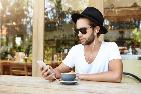 Attractive young male with stubble using online app on his cell phone, enjoying free wireless high speed internet connection and listening to music or audio book while drinking cappuccino at cafe