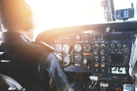 Adult airplane pilot wearing headset and outfit performing his job, sitting inside aircraft cockpit at steering control with modern dashboard. Bright sunshine penetrating into cabin through glass