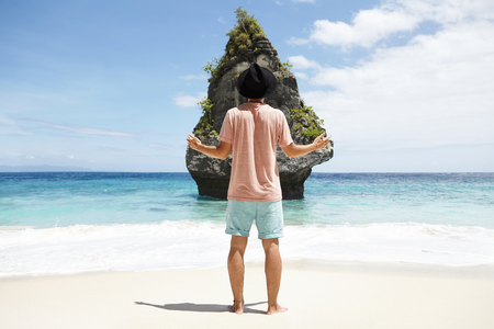 Back view of young traveler in black hat standing barefooted on sandy beach in front of rocky cliff, keeping his hands stretched as he admires beautiful place which he was looking for a long time Stock Photo