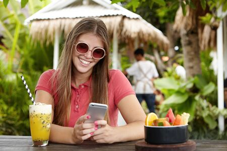 Happy woman making video call to her boyfriend, using free wi-fi on her mobile phone, looking at screen with joyful flirting smile, sharing best moments of her long-awaited holidays with him
