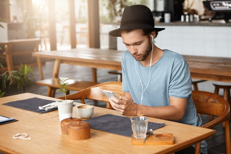 newsfeed: Fashionable young bearded man in black hat checking his newsfeed on social media and listening to songs online on earphones, using music app on his cell phone, enjoying free wi-fi during lunch at cafe
