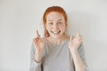Headshot of superstitious redhead girl keeping her fingers crossed, making wish, sincerely believing in her success or victory. Beautiful freckled young woman hoping her dreams will come true