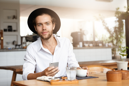 tabla de surf: Human and modern technology concept. Portrait of handsome young Caucasian student in black hat and white shirt, surfing internet on his smart phone, enjoying free wireless connection during lunch