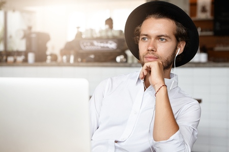 Pensive young bearded businessman wearing white shirt and black hat touching his chin and looking ahead of him with faint smile, using laptop to listen to his favorite music online in earphones