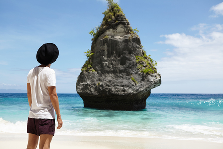 Cropped rear shot of fashionable male model wearing black hat, t-shirt and shorts standing on sand in front of rocky cliff in middle of ocean while posing on beach for travel magazine on sunny day
