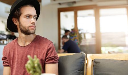 Indoor portrait of handsome hipster in t-shirt with rolled up sleeves relaxing alone at cafe and looking at something ahead of him with faint smile, sitting against blurred window background