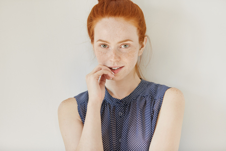 People, youth and tenderness concept. Portrait of young redhead female model wearing sleeveless shirt with spots having shy cute smile, holding hand on her lips and looking at camera, posing indoors Banco de Imagens