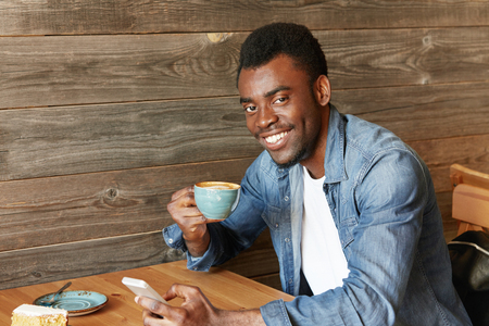 newsfeed: Happy cheerful African student holding mug, drinking fresh cappuccino, browsing internet and checking newsfeed on social media, using cell phone during coffee break at modern cafe with wooden walls