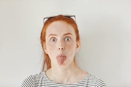 Retrato de pelirrojo divertido joven mujer de raza caucásica con pecas que se divierten dentro de casa, sacando la lengua en la cámara. Primer plano de adolescente llevaba camisa de marinero de moda haciendo caras en la pared blanca Foto de archivo - 70986559
