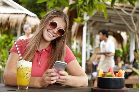 newsfeed: People, modern technology and communication concept. Pretty girl in trendy shades texting friends, checking newsfeed via social media while surfing internet at cafe, enjoying free wireless connection