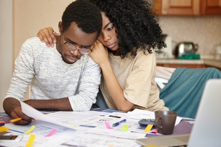 Unhappy young African couple facing financial stress: black man in spectacles holding notification informing that bank denied to prolong loan term, his beautiful wife embracing him supportively