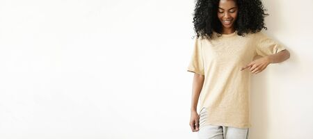 oversize: Indoor shot of beautiful young African woman with cute smile looking down and pointing at copy space on her oversize ripped t-shirt. Cheerful dark-skinned girl dressed casually posing at studio wall