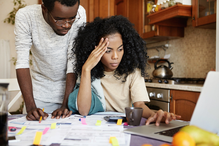 Serious young dark-skinned female with Afro hairstyle sitting in front of open laptop, using online banking app to review family accounts while analyzing domestic budget together with her husband Banco de Imagens
