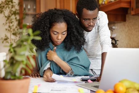 Young dark-skinned couple managing domestic budget and paying bills using online banking app on generic laptop. Wife with piece of paper calculating family expenses together with her husband