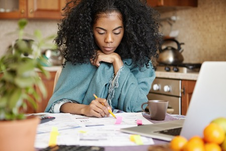 Indoor shot of beautiful young African housewife holding pencil, filling in papers while managing family budget and calculating expenses, sitting at kitchen table in front of open laptop computer Stock Photo