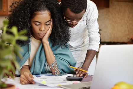 Young African family dealing financial issues. Serious woman sitting in front of open laptop computer, looking through bills while her husband in spectacles making calculations on calculator