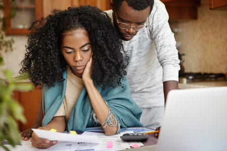 eviction: Stressed African couple having many debts trying to cut their domestic expenses to save money and pay off loan in bank. Worried wife holding piece of paper and reading notification about eviction