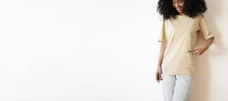 oversize: Cropped shot of beautiful young dark-skinned woman with charming pretty smile posing at blank white studio wall, pointing her index finger at copy space on her ripped oversize t-shirt and smiling Stock Photo