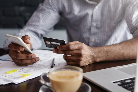 Close up shot of African mans hands holding mobile and credit card. Dark-skinned businessman checking account balance, using online banking application on his cell phone, drinking coffee at cafe